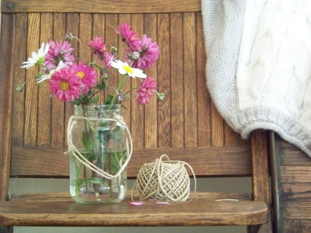 wooden bench with sweater and flowers