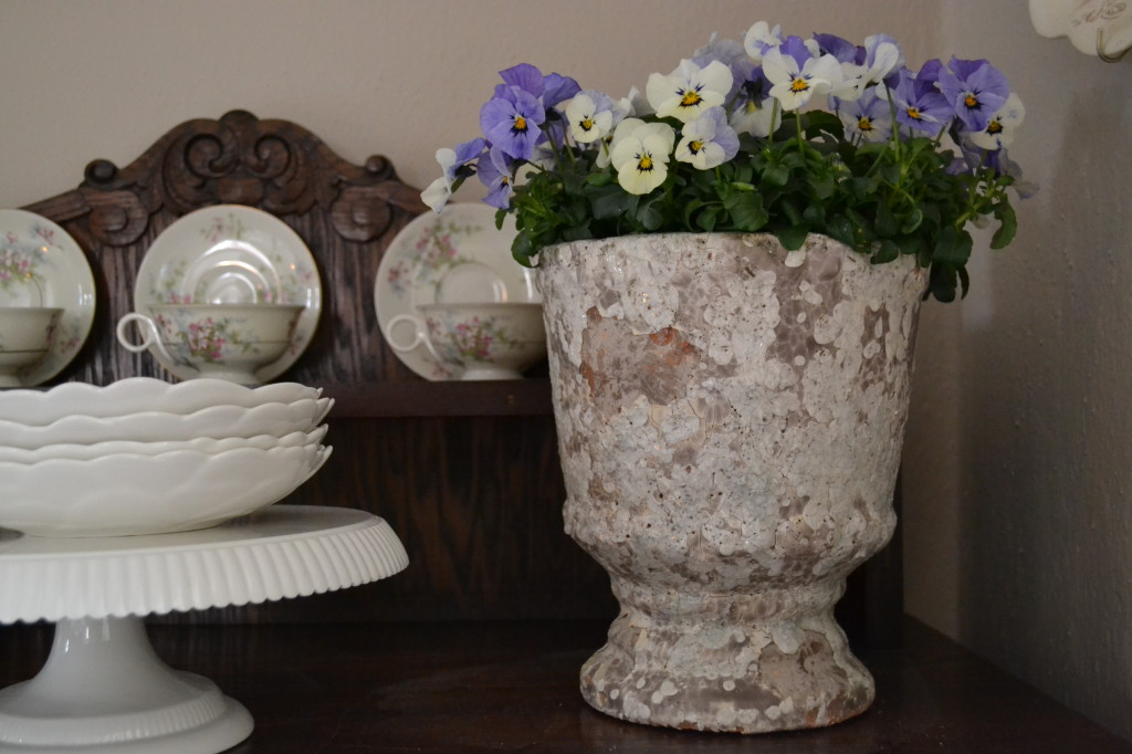 chippy clay pot and violas on buffet