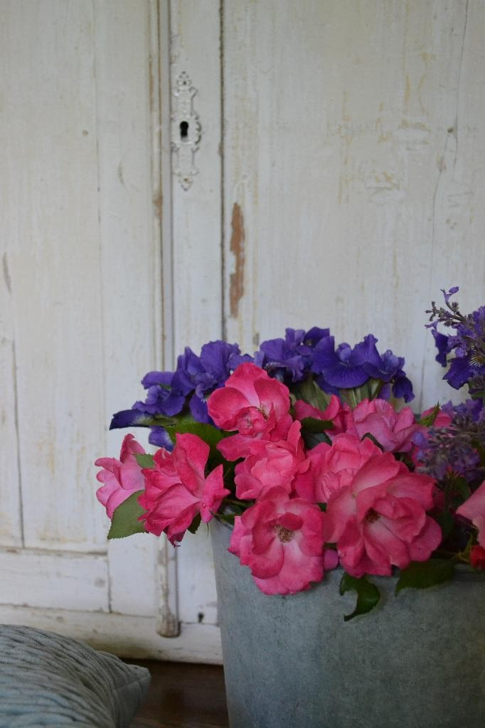 bucket of blooms with a distressed cupboard