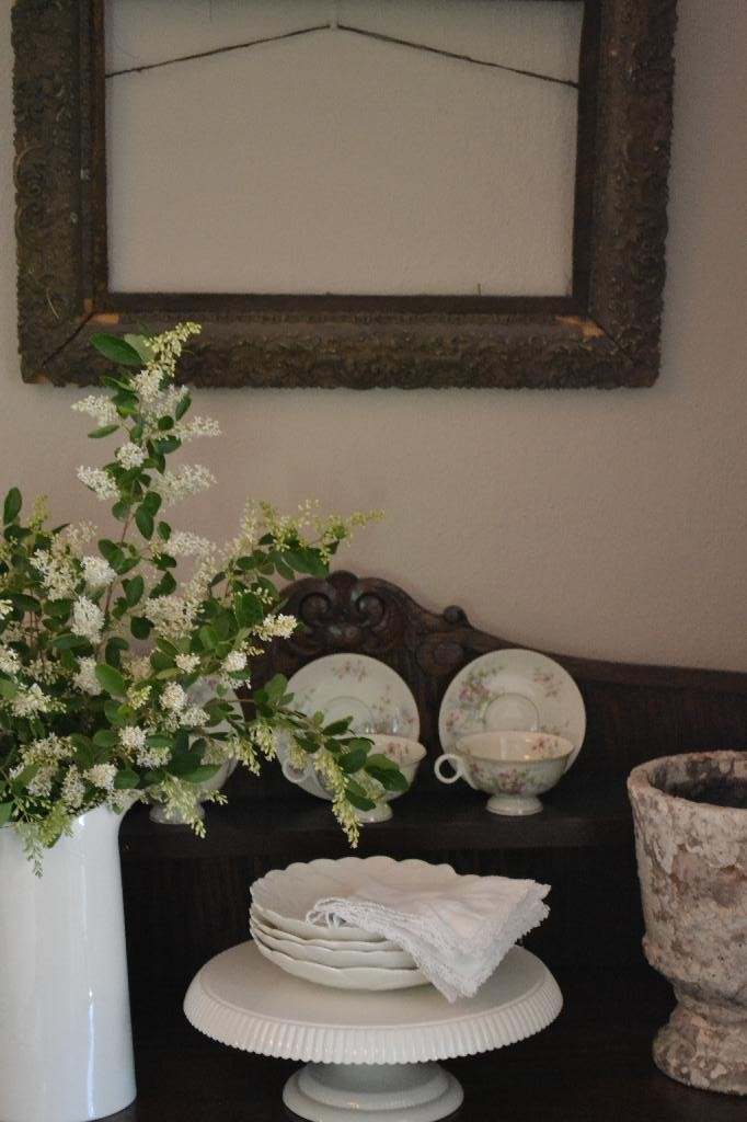cottage hutch with white dishes and a shabby frame