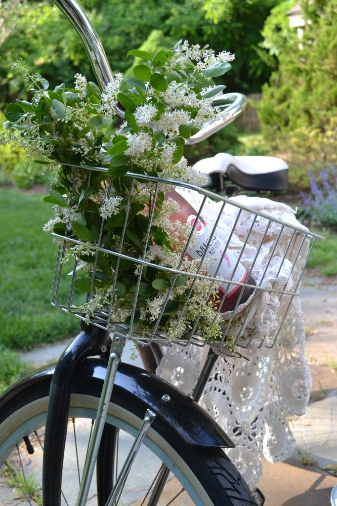 bike basket filled with flowering branches, wine, and crochet