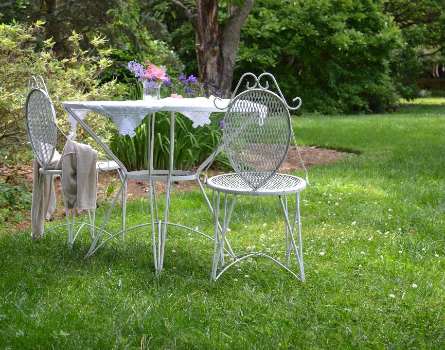 a vintage table and chairs in the garden