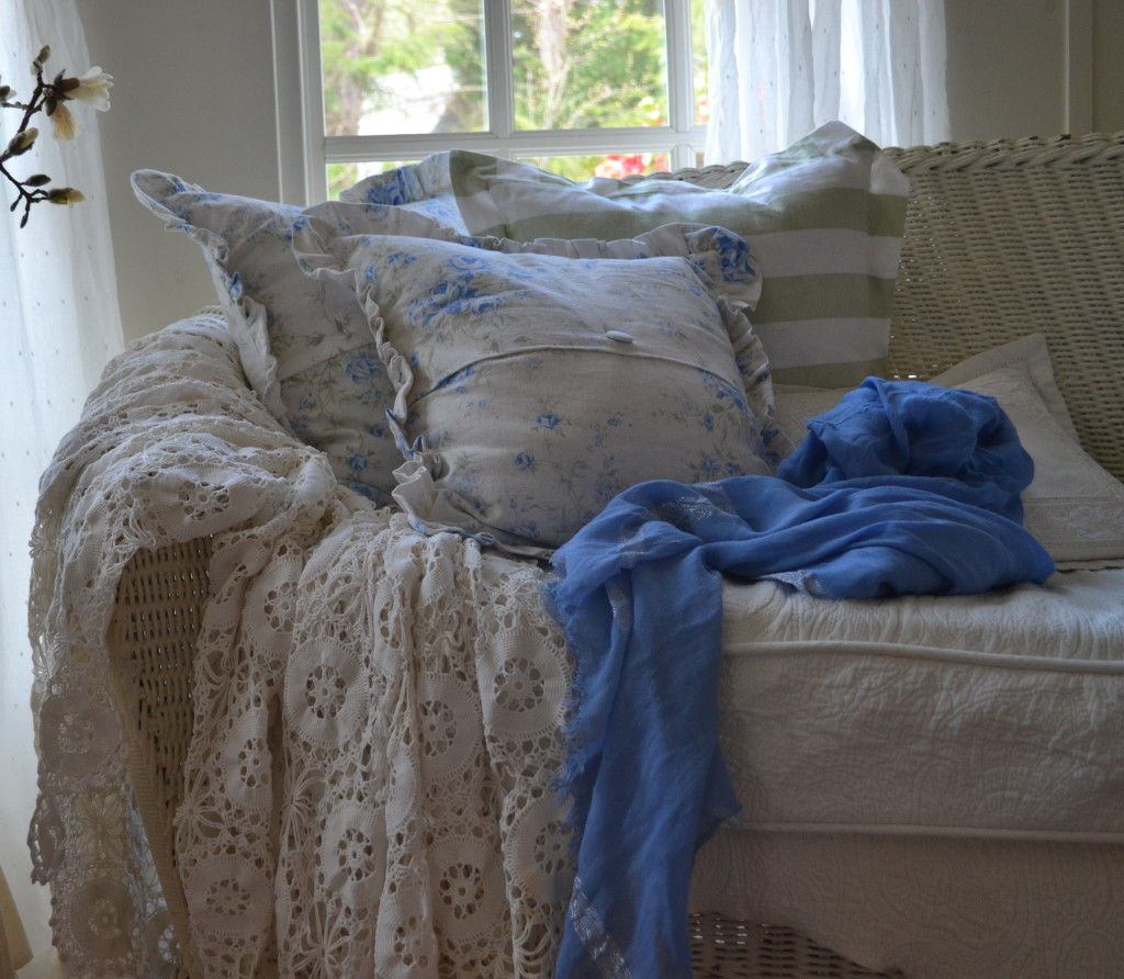 white wicker settee with a pile of shabby chic pillows