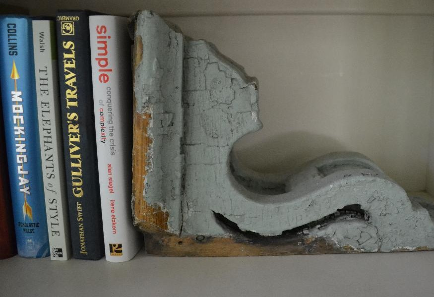 sage green chippy distressed corbel used as a bookend