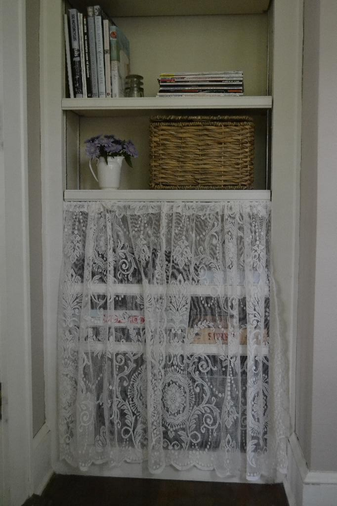 bookcase with a lace curtain to hide clutter
