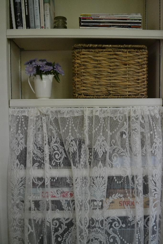 bookcase with basket, flowers, and a lace curtain