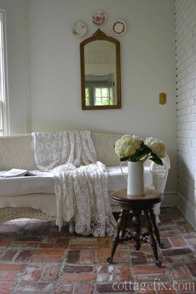 Cottage Fix - sun porch with white wicker, brick flooring, and hydrangea blooms