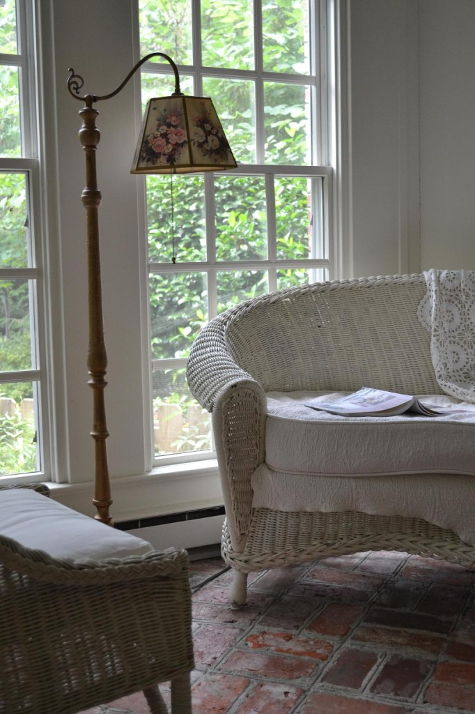 Cottage Fix - sun porch with gold lamp and white wicker