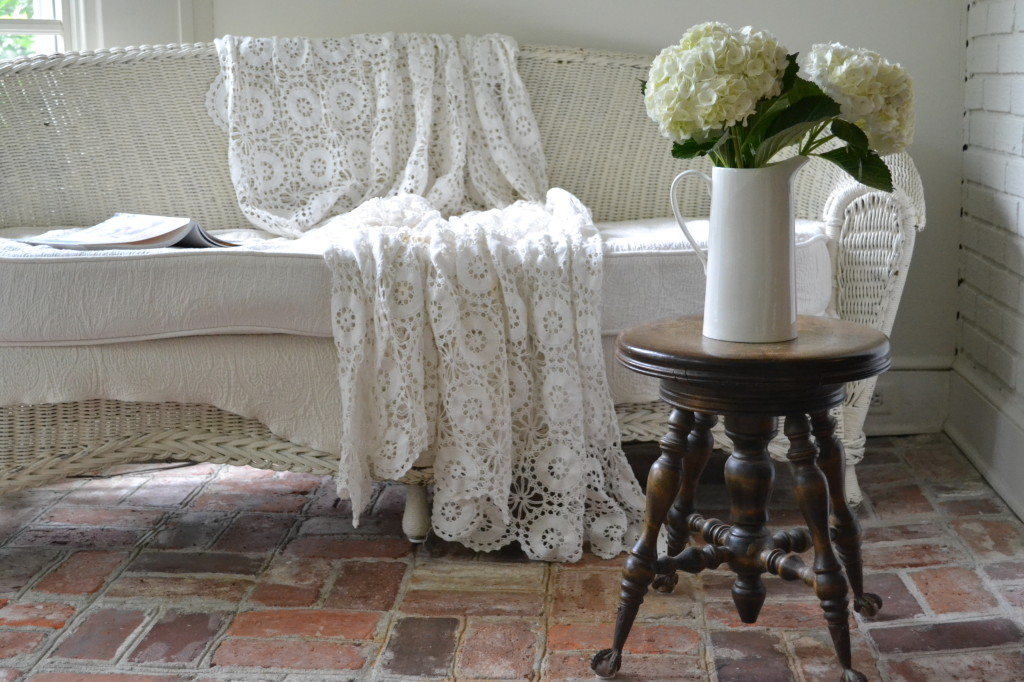 Cottage Fix - sun porch with white wicker, crochet, and brick floors