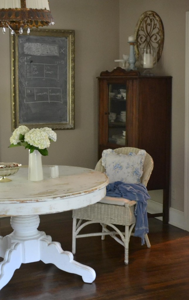 Cottage Fix - dining room table with white wicker chair and bright blue accessories