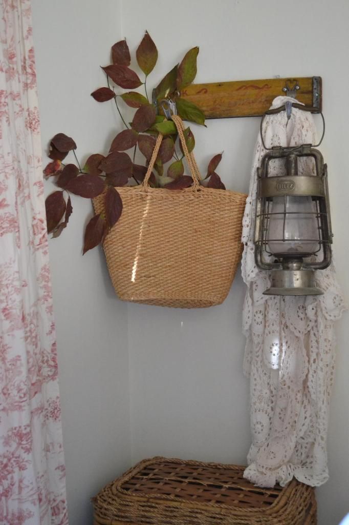 Cottage Fix - row of hooks with a vinatge lantern, straw bag, and crochet