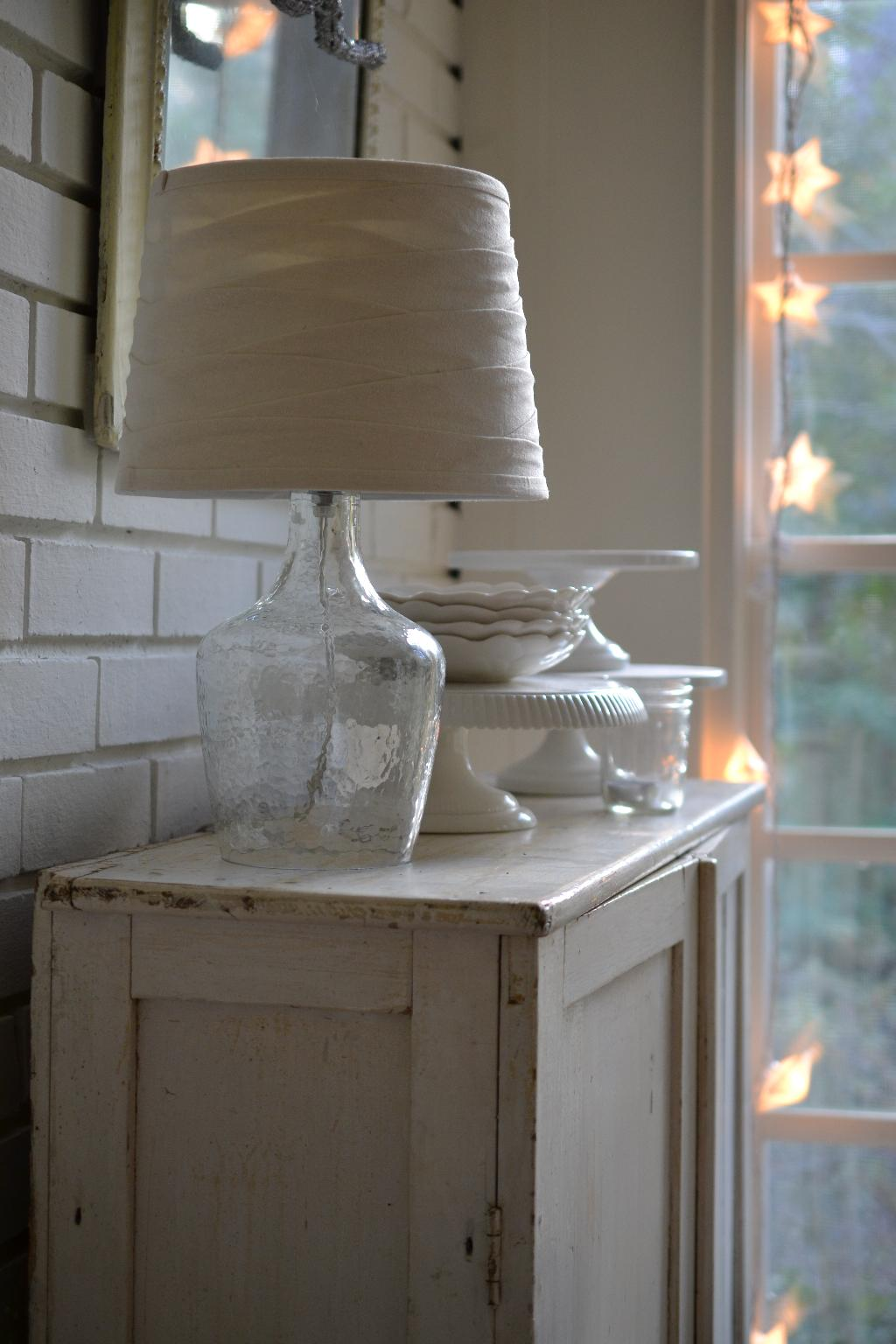 Cottage Fix - cupboard with white cake plates and lamp