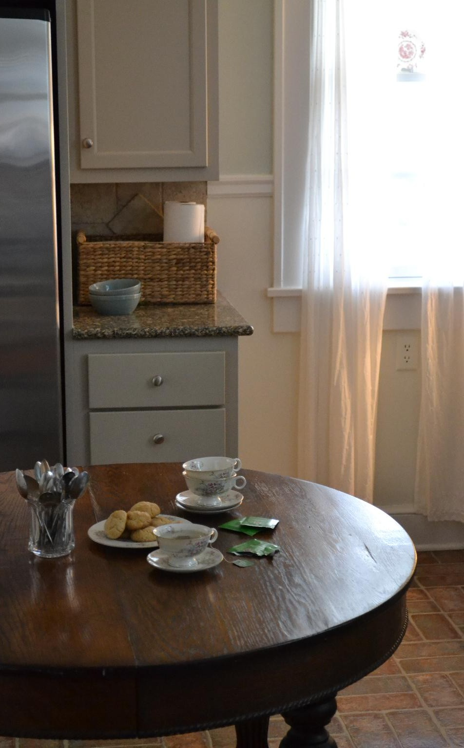 Cottage Fix - kitchen with wooden table and light curtains