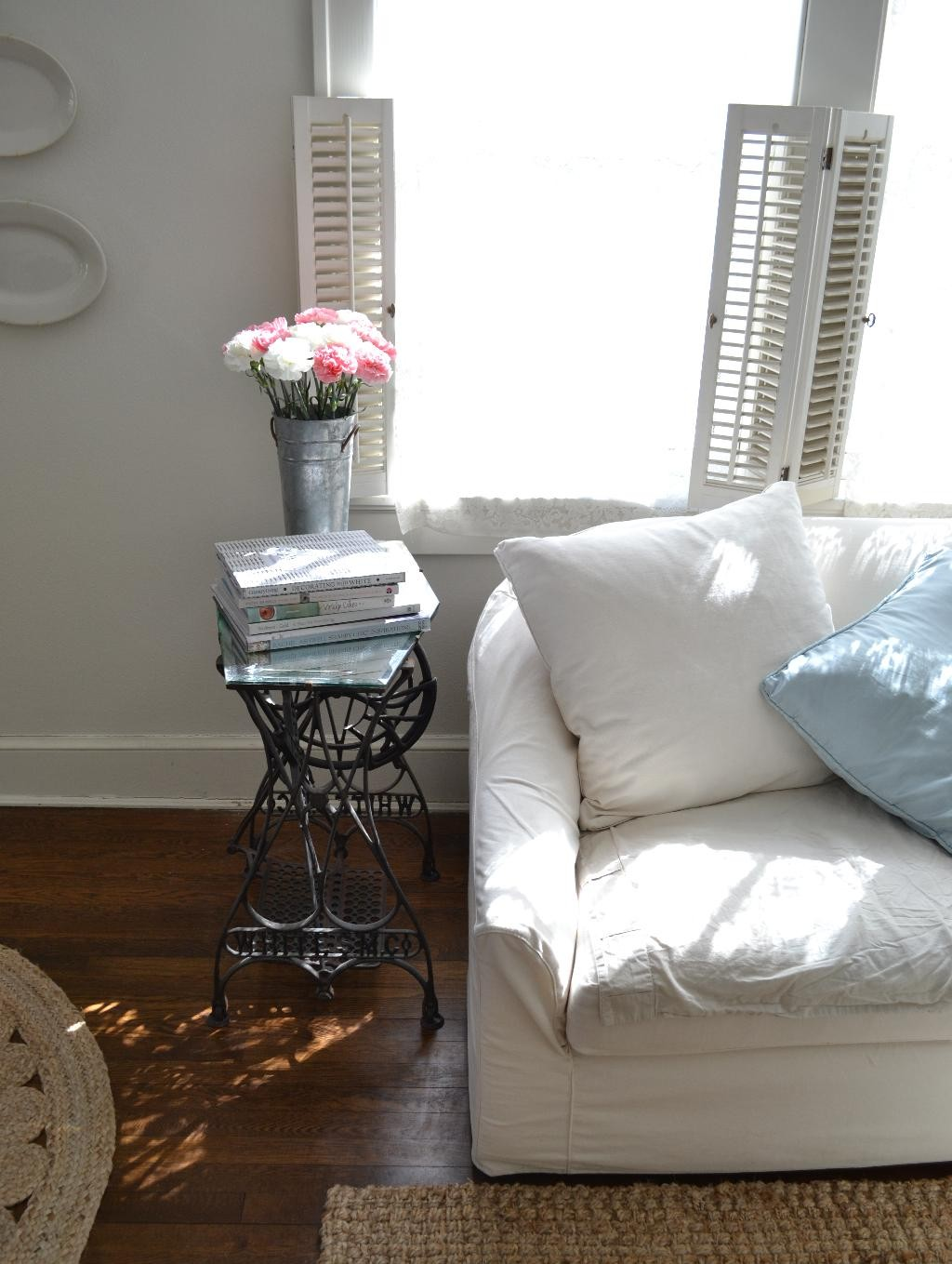 Cottage Fix - vintage sewing machine side table, white sofa, and carnations