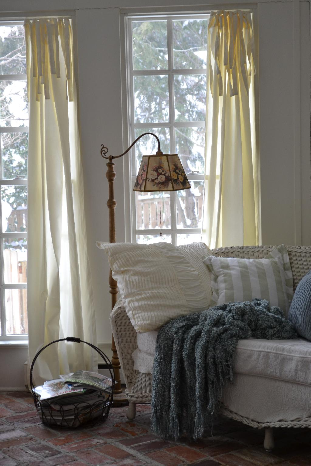 Cottage Fix - snow in the garden, wicker, pile of pillows and a blue blanket