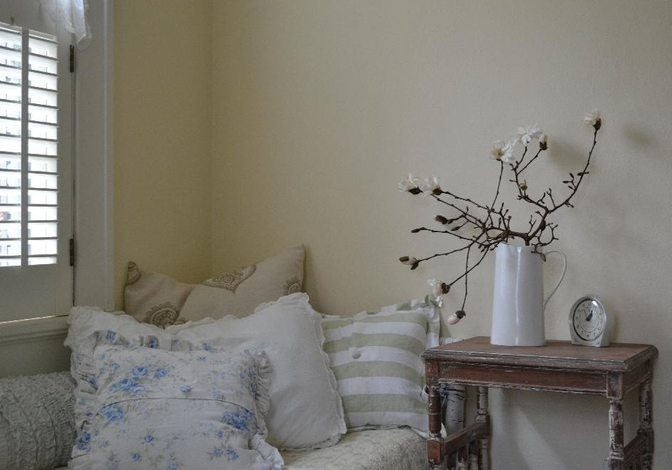 Cottage Fix - guest room with a pile of pillows and blooming branches