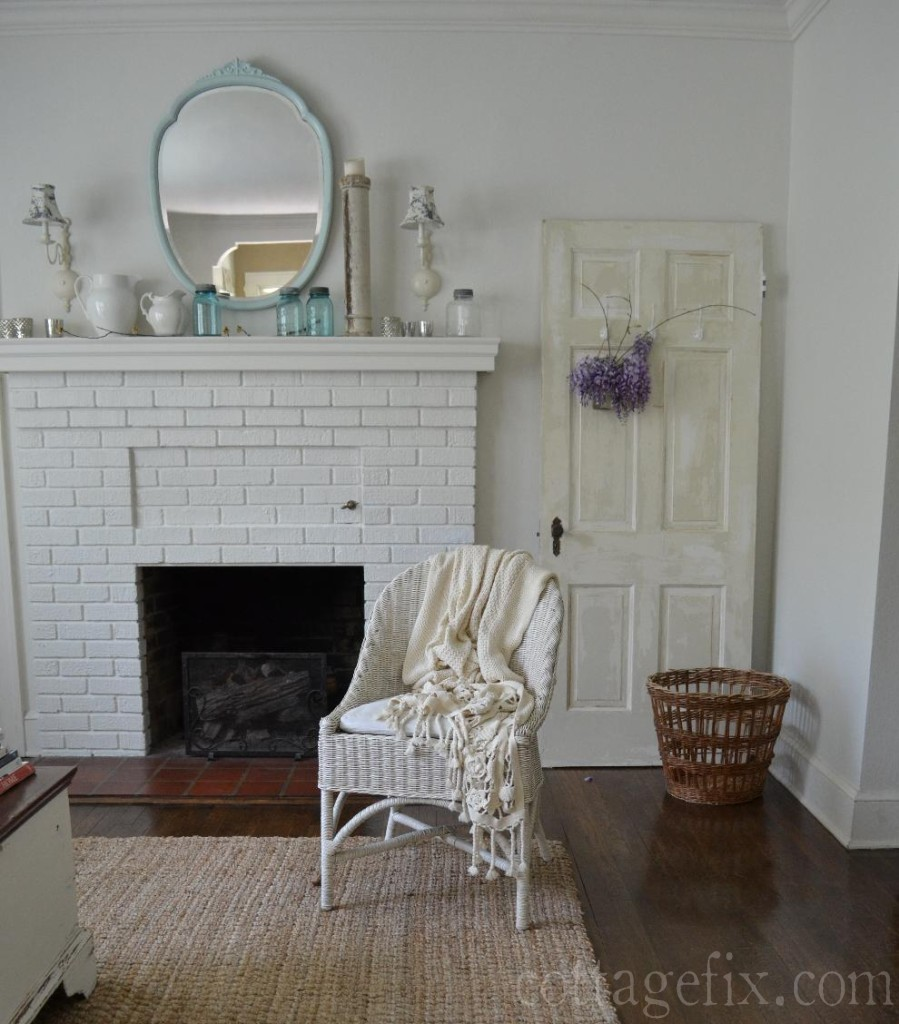 Cottage Fix blog - living room with wicker, chippy door, and wisteria