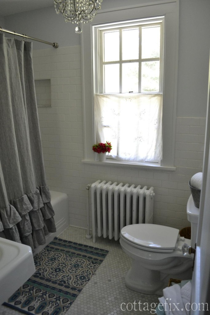 Cottage Fix blog - cottage bathroom with white subway tiles, crystal chandlier, and gray ruffled shower curtain