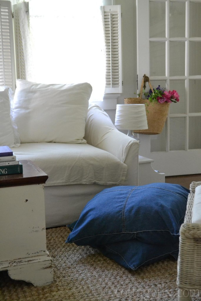 Cottage Fix blog - white slip sofa, denim floor pillows, and a straw tote full of flowers