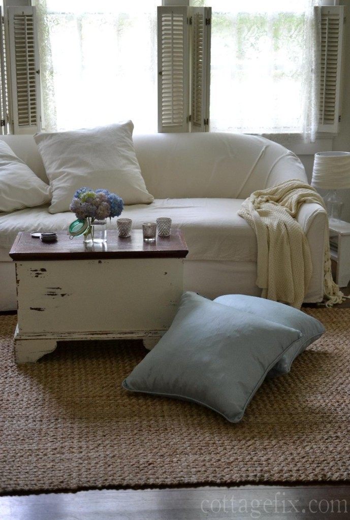 Cottage Fix blog - living room with white slip sofa, blue floor pillows, and a canning jar filled with hydrangea