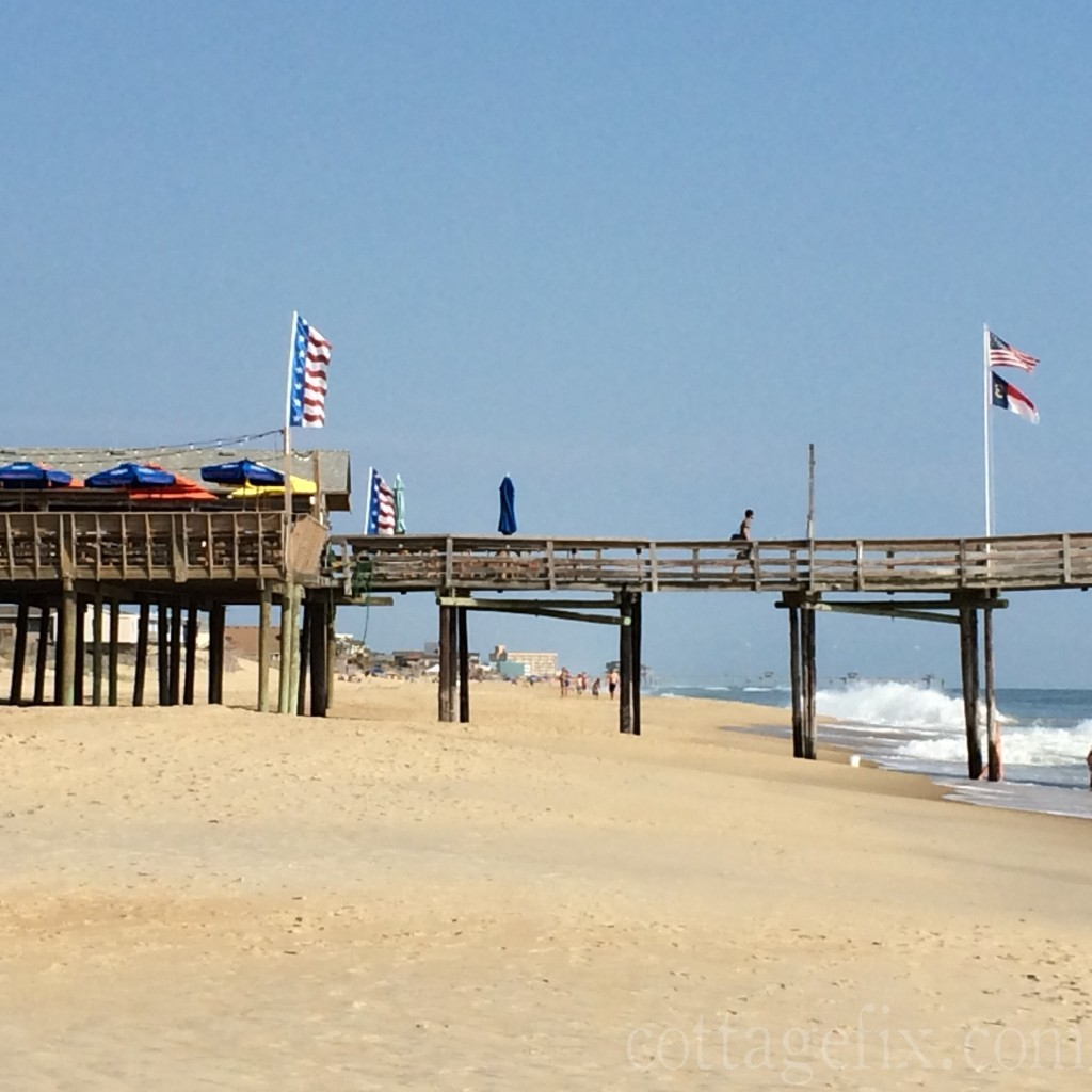 Cottage Fix blog - the pier with colorful flags in South Nags Head, NC
