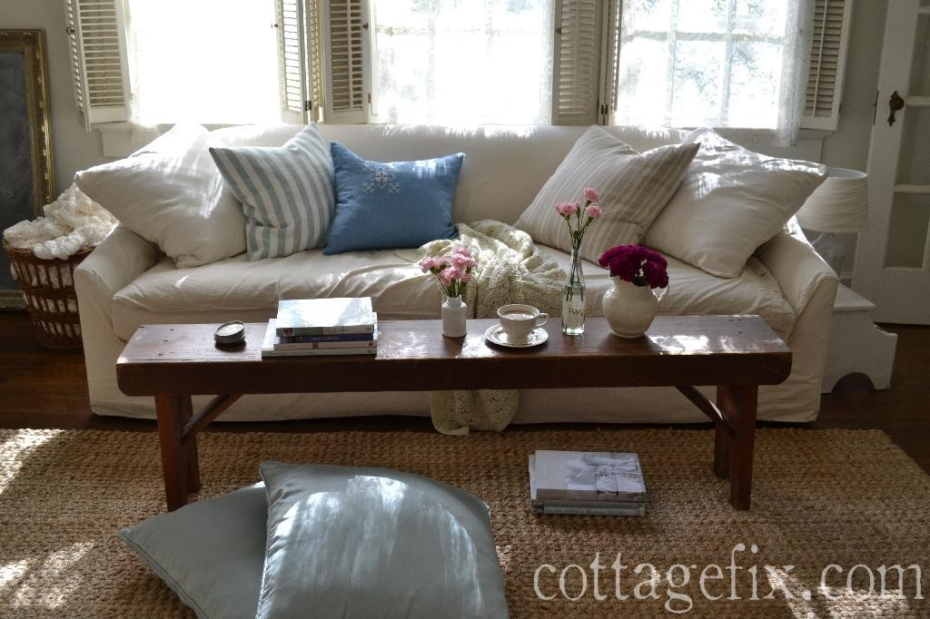 Cottage Fix blog - cottage living room with white sofa, farmhouse bench , and blue floor pillows