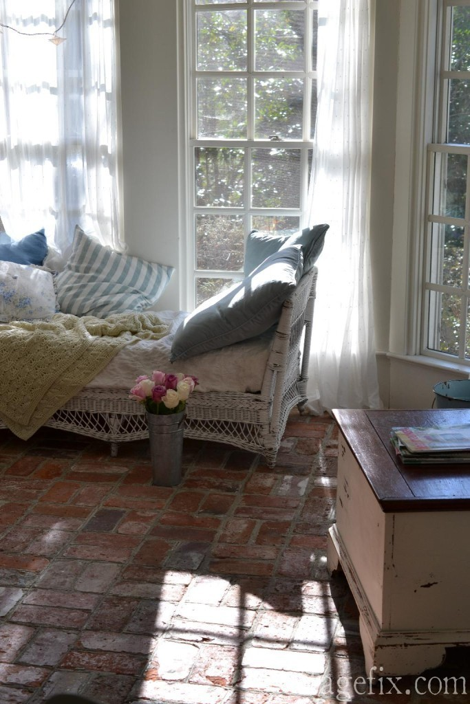 Cottage Fix blog - sun porch with brick floors, white wicker, and shabby chic pillows
