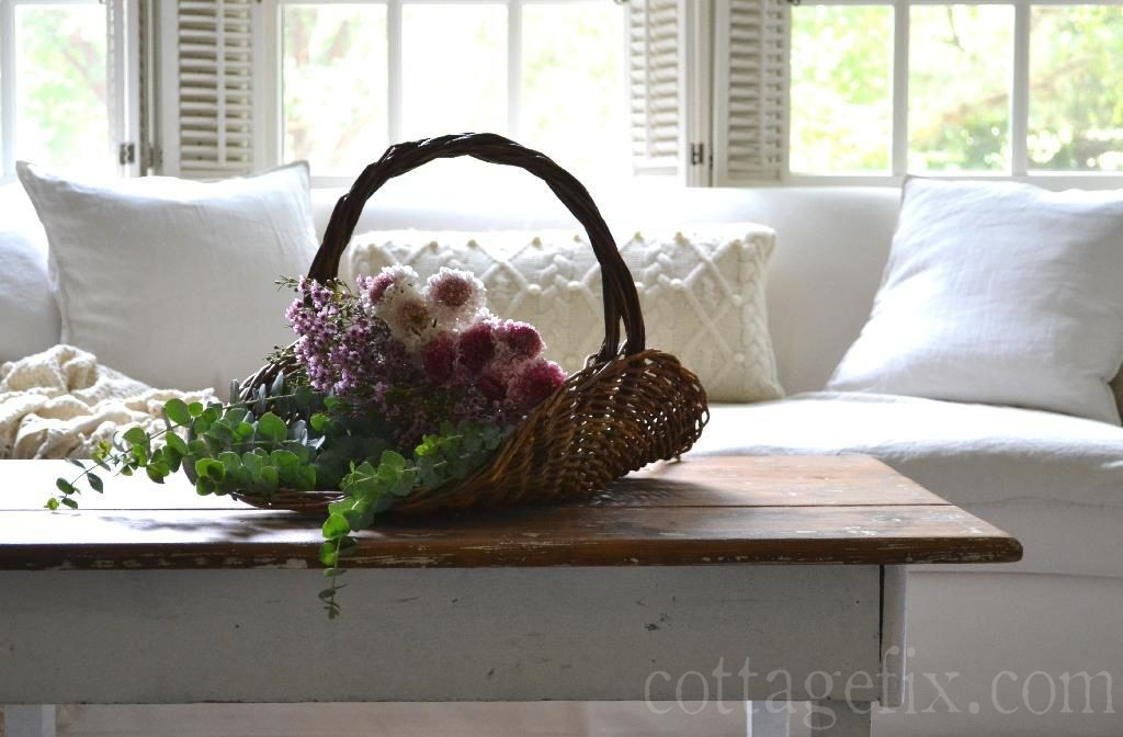Cottage Fix blog - gathering basket filled with bright blooms on cottage coffee table